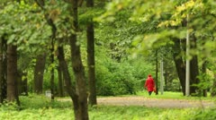 Adult woman in a red coat is along the alley Stock Footage