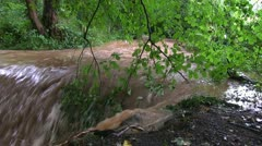 Flood water flowing over waterfall on Wesley Brook, Shifnal, Shropshire, England Stock Footage