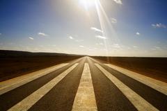 long straight road and runway markings - stock photo
