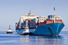 Laden container ship entering port with tugs and pilot cutter Stock Photos