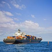 heavily laden container ship leaving port - stock photo