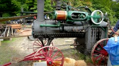 A steam engine tractor generates power to operate a pony saw mill. Stock Footage
