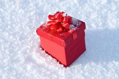 Red gift box on snow Stock Photos