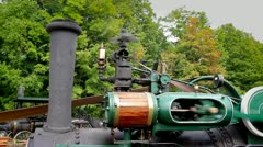 An old-fashioned steam engine tractor creates power to drive a pony saw mill. Stock Footage