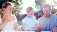 Mother Feeding Pizza Slice to Toddler at Picnic Outdoors Stock Footage