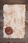 old paper with a wax seal on wood texture - stock photo