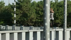 Girl jumps on a granit fence Stock Footage