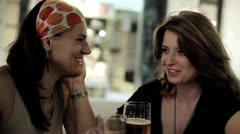 Female friends in restaurant drinking beer in the evening, steadycam shot Stock Footage
