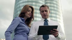 Businesspeople consulting something in front of skyscrapers Stock Footage