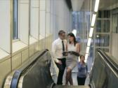 Business people on escalator, discussing business issues Stock Footage