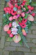 pink sympathy bouquet on pavement - stock photo