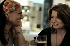 Female friends in restaurant drinking beer in the evening, steadycam shot - stock footage