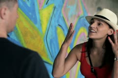 Arguing couple standing in front of graffiti, steadycam shot Stock Footage