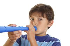 Boy blowing blue horn Stock Photos