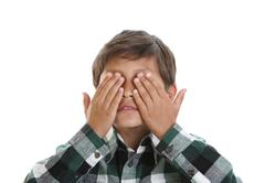 young boy covers his eyes - stock photo