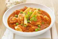 Stew chicken casserole with peas and baby sweetcorn Stock Photos
