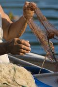 Fisherman`s hands and the fishing net - stock photo