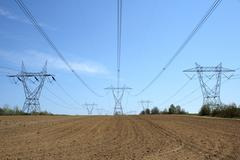 Electricity pylons in cultivated land - stock photo