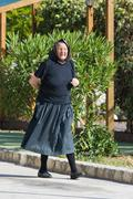 Old lady walking down the street with the rose bay on island Krapanj Stock Photos
