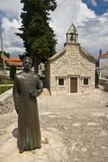 Statue and a chapel in Primosten - stock photo