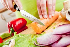 woman's hands cutting vegetables - stock photo