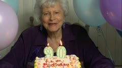 Senior Woman Blows Out Cake Candles Stock Footage
