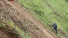 Biker climbs on hill to motorcycle from which he fell Stock Footage