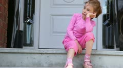 Little girl is bored when sits on porch near door of cottage Stock Footage