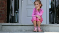 Little girl supports her head when sits on porch near door Stock Footage