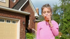 Little girl drinks juce from glass and smiles near cottage Stock Footage