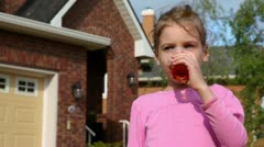 Little girl drinks juce and smiles near cottage at summer day Stock Footage