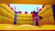 Stock Video Footage of Two kids boy and little girl jump at inflatable playground
