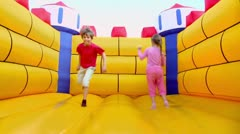 Pair of children boy and girl jump at inflatable playground Stock Footage