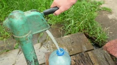 Hand push handle of street water pump and fills plastic bottle - stock footage