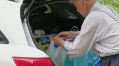 Old man puts several bottle with water to car boot Stock Footage