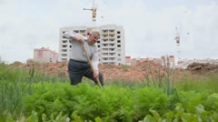 Man puts earth up by spade on seedbeds near construction site Stock Footage