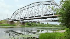 Goods train ride at bridge over river at summer day Stock Footage