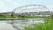 Goods train with many wagons ride at bridge over river Stock Footage