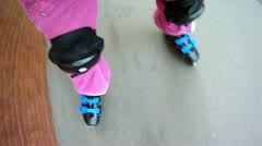Little girl rollerblading on paved road near brick wall Stock Footage