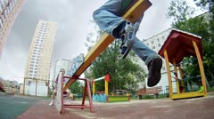 Girl and boy goes for a drive on a teeter board Stock Footage