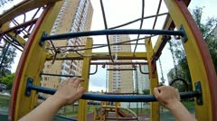 Boy rises on an iron ladder at playground Stock Footage