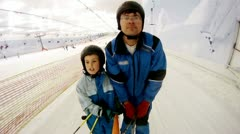 Father with son rise on skilift in ski complex Stock Footage