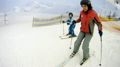 Son with mother learn to ski in yearround ski complex Stock Footage