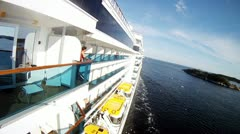 Passengers stand along on balconies of liner floating Stock Footage