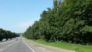 Road running towards with cars and trees around on day Stock Footage