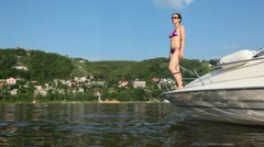 Woman stands on brink of boat on river and swings hands Stock Footage
