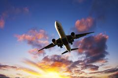 Jet aeroplane landing from bright dramatic moody sunset sky Stock Photos