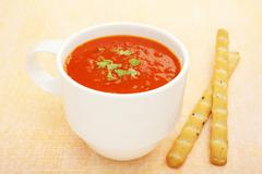 cup mug low fat tomato soup bread sticks coloured background - stock photo