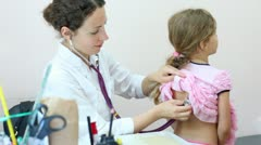 Woman listens to back of little girl in policlinic Stock Footage
