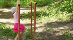 Girl in dress shakes on hands iron bars in middle of grass Stock Footage
